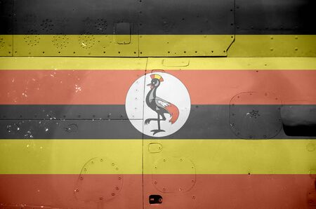 Uganda flag depicted on side part of military armored helicopter close up. Army forces aircraft conceptual background 스톡 콘텐츠