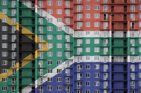 South Africa flag depicted in paint colors on multi-storey residental building under construction. Textured banner on big brick wall background Reklamní fotografie