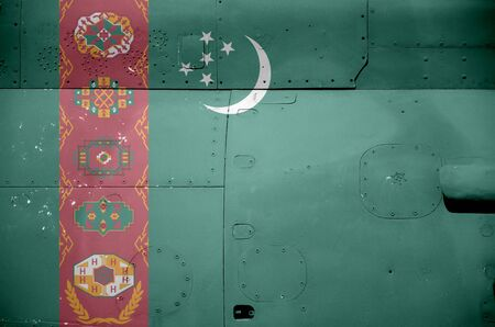 Turkmenistan flag depicted on side part of military armored helicopter close up. Army forces aircraft conceptual background 스톡 콘텐츠
