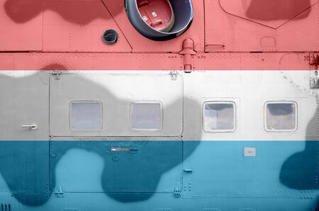 Luxembourg flag depicted on side part of military armored helicopter close up. Army forces aircraft conceptual background