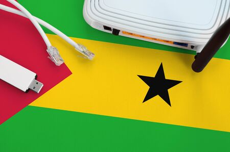 Sao Tome and Principe flag depicted on table with internet rj45 cable, wireless usb wifi adapter and router. Internet connection concept