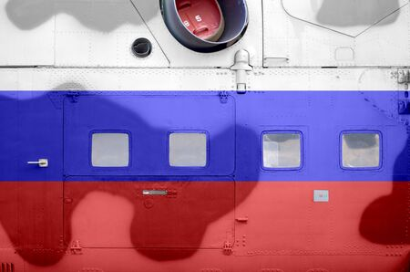 Russia flag depicted on side part of military armored helicopter close up. Army forces aircraft conceptual background 스톡 콘텐츠