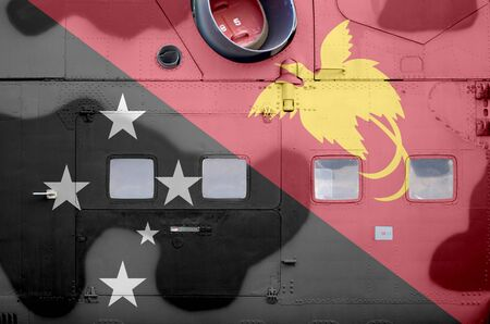 Papua New Guinea flag depicted on side part of military armored helicopter close up. Army forces aircraft conceptual background