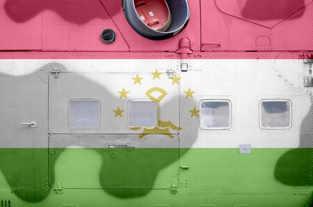 Tajikistan flag depicted on side part of military armored helicopter close up. Army forces aircraft conceptual background 스톡 콘텐츠