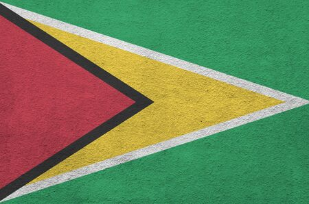 Guyana flag depicted in bright paint colors on old relief plastering wall close up. Textured banner on rough background