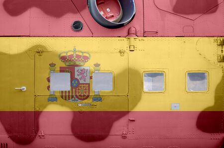 Spain flag depicted on side part of military armored helicopter close up. Army forces aircraft conceptual background 스톡 콘텐츠