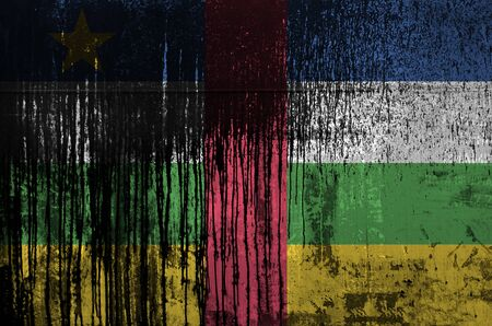 Central African Republic flag depicted in paint colors on old and dirty oil barrel wall close up. Textured banner on rough background