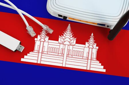 Cambodia flag depicted on table with internet rj45 cable, wireless usb wi-fi adapter and router. Internet connection concept