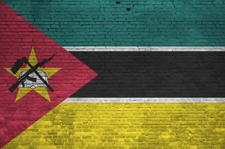 Mozambique flag depicted in paint colors on old brick wall close up. Textured banner on big brick wall masonry background