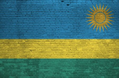 Rwanda flag depicted in paint colors on old brick wall close up. Textured banner on big brick wall masonry background
