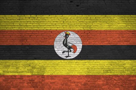 Uganda flag depicted in paint colors on old brick wall close up. Textured banner on big brick wall masonry background Stockfoto