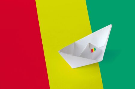 Guinea flag depicted on paper origami ship closeup. Oriental handmade arts concept
