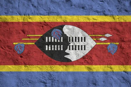 Swaziland flag depicted in bright paint colors on old relief plastering wall close up. Textured banner on rough background Stock fotó