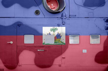 Haiti flag depicted on side part of military armored helicopter close up. Army forces aircraft conceptual background