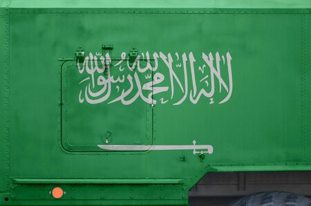 Saudi Arabia flag depicted on side part of military armored truck close up. Army forces vehicle conceptual background