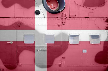 Denmark flag depicted on side part of military armored helicopter close up. Army forces aircraft conceptual background