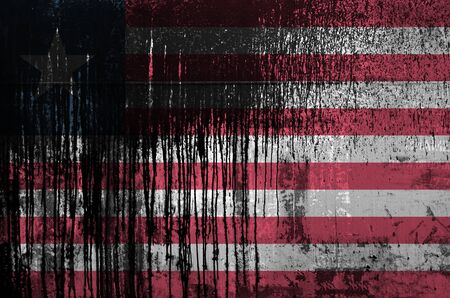 Liberia flag depicted in paint colors on old and dirty oil barrel wall close up. Textured banner on rough background