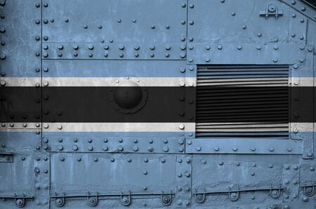 Botswana flag depicted on side part of military armored tank close up. Army forces conceptual background 스톡 콘텐츠