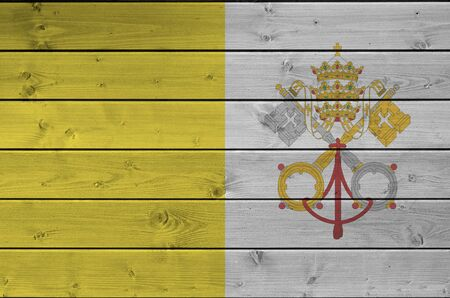 Vatican City State flag depicted in bright paint colors on old wooden wall close up. Textured banner on rough background