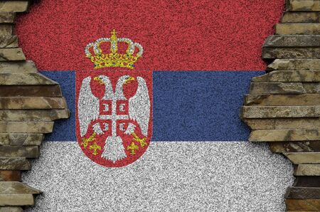 Serbia flag depicted in paint colors on old stone wall close up. Textured banner on rock wall background