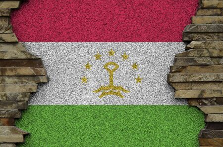 Tajikistan flag depicted in paint colors on old stone wall close up. Textured banner on rock wall background