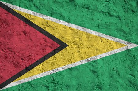 Guyana flag depicted in bright paint colors on old relief plastering wall close up. Textured banner on rough background Stock fotó