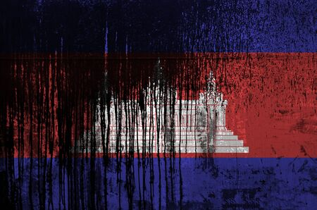 Cambodia flag depicted in paint colors on old and dirty oil barrel wall close up. Textured banner on rough background