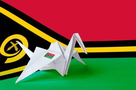 Vanuatu flag depicted on paper origami crane wing. Oriental handmade arts concept Banco de Imagens