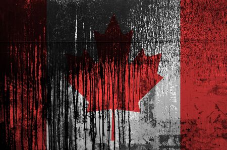 Canada flag depicted in paint colors on old and dirty oil barrel wall close up. Textured banner on rough background Reklamní fotografie