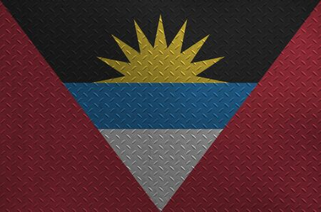 Antigua and Barbuda flag depicted in paint colors on old brushed metal plate or wall close up. Textured banner on rough background
