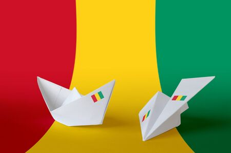 Guinea flag depicted on paper origami airplane and boat. Oriental handmade arts concept
