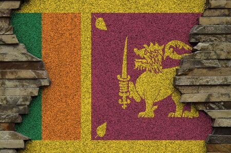 Sri Lanka flag depicted in paint colors on old stone wall close up. Textured banner on rock wall background