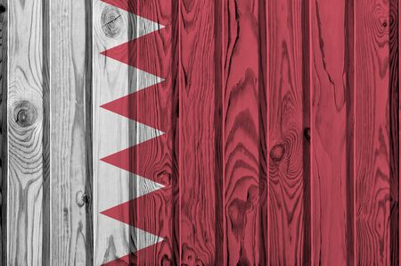 Bahrain flag depicted in bright paint colors on old wooden wall close up. Textured banner on rough background