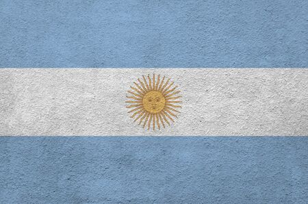 Argentina flag depicted in bright paint colors on old relief plastering wall close up. Textured banner on rough background
