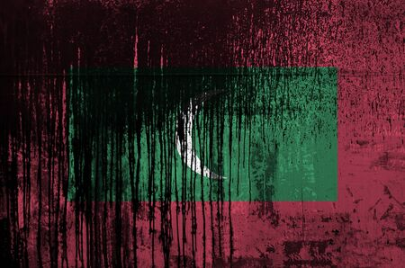 Maldives flag depicted in paint colors on old and dirty oil barrel wall close up. Textured banner on rough background