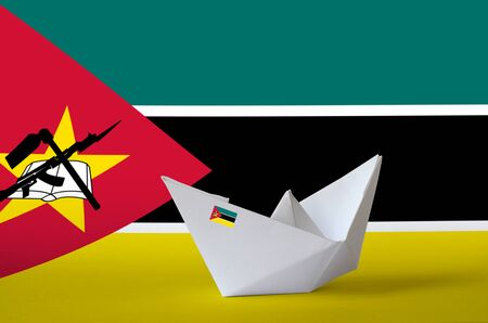 Mozambique flag depicted on paper origami ship closeup. Oriental handmade arts concept