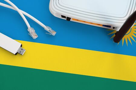 Rwanda flag depicted on table with internet rj45 cable, wireless usb wifi adapter and router. Internet connection concept Foto de archivo