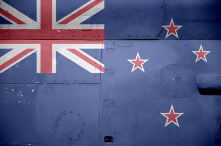 New Zealand flag depicted on side part of military armored helicopter close up. Army forces aircraft conceptual background