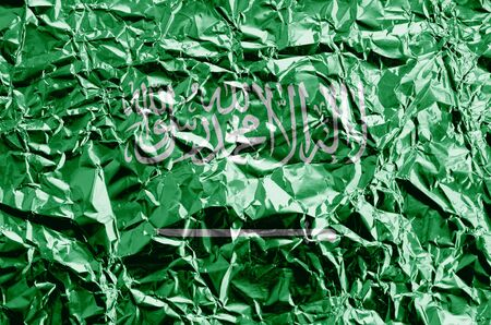 Saudi Arabia flag depicted in paint colors on shiny crumpled aluminium foil close up. Textured banner on rough background