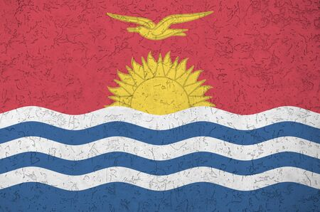 Kiribati flag depicted in bright paint colors on old relief plastering wall close up. Textured banner on rough background