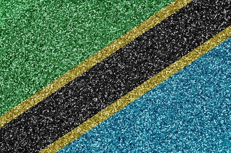 Tanzania flag depicted on many small shiny sequins. Colorful festival background for disco party