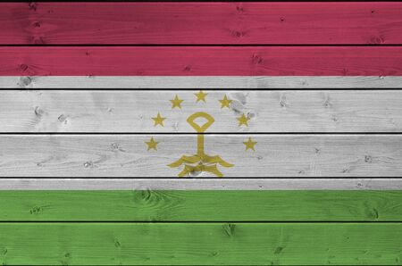 Tajikistan flag depicted in bright paint colors on old wooden wall close up. Textured banner on rough background Stock fotó