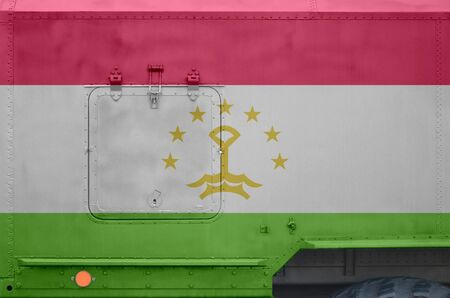 Tajikistan flag depicted on side part of military armored truck close up. Army forces vehicle conceptual background Stock fotó