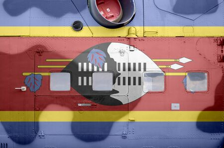 Swaziland flag depicted on side part of military armored helicopter close up. Army forces aircraft conceptual background Stock fotó