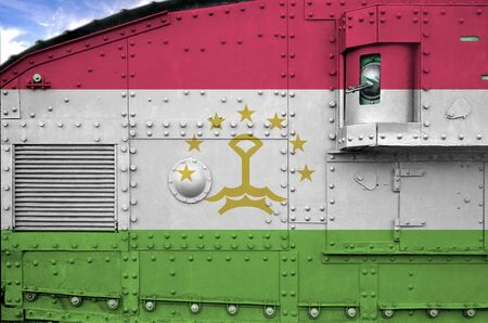 Tajikistan flag depicted on side part of military armored tank close up. Army forces conceptual background