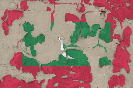 Maldives flag depicted in paint colors on old obsolete messy concrete wall close up. Textured banner on rough background