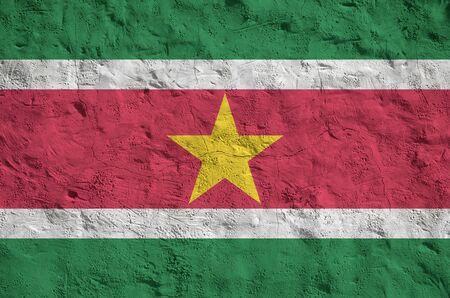 Suriname flag depicted in bright paint colors on old relief plastering wall close up. Textured banner on rough background Stock fotó
