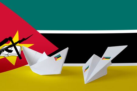 Mozambique flag depicted on paper origami airplane and boat. Oriental handmade arts concept