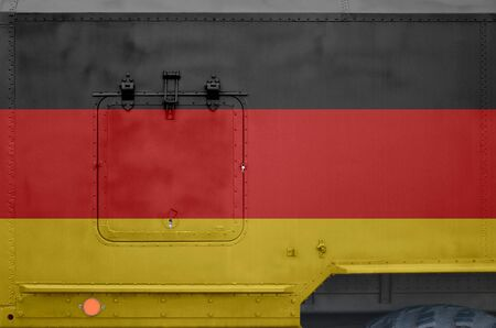 Germany flag depicted on side part of military armored truck close up. Army forces vehicle conceptual background