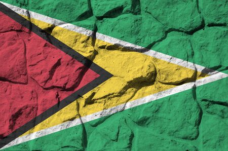 Guyana flag depicted in paint colors on old stone wall close up. Textured banner on rock wall background Stock fotó
